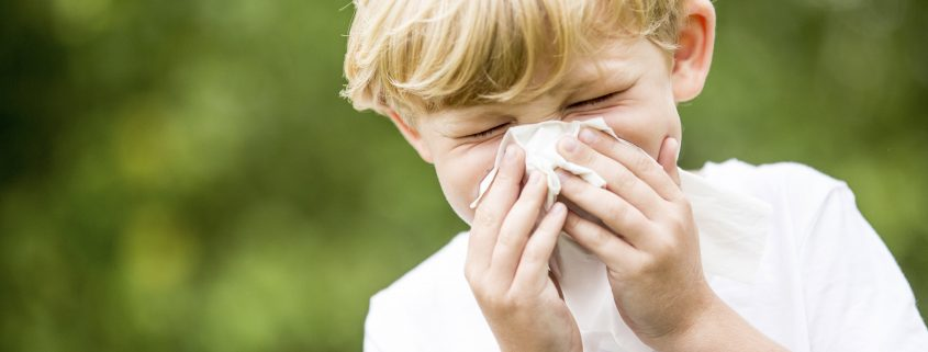 boy sneezing due to allergic asthma